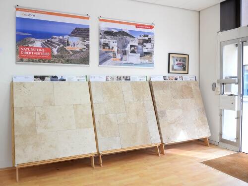 Drei Mustertafeln mit verschiedenen Travertinsorten lehnen an einer weißen Wand